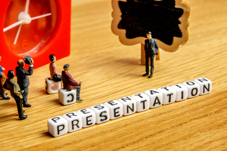 little miniature figurines with little dices forming specific word as a part of team meeting collection pictures dedicated to one part of its time table on wooden background