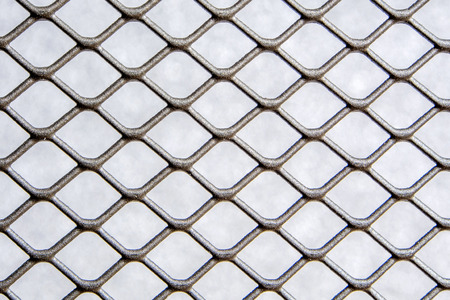 closeup of silver grey color metal wire mesh fence with light grey background shade