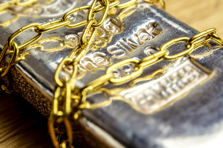 closeup of silver brick in golden chains laying on wooden background
