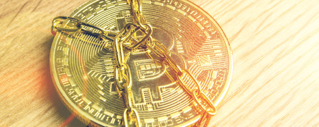 closeup of golden bitcoin in golden chains laying on wooden background