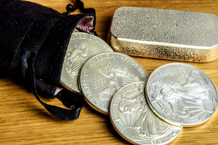 closeup of silver coins american one ounce eagles and brick falling out of black money bag and laying on wooden background Banco de Imagens