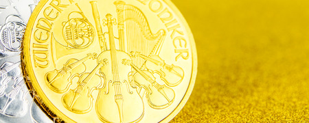 closeup of silver and golden austrian phillharmonikers one ounce coins on golden background placed on left side