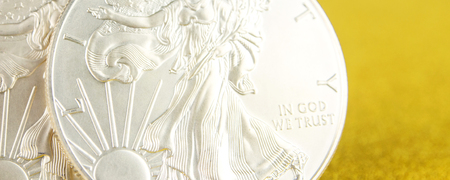 closeup of silver eagle and golden american eagle one ounce coins on golden background placed on left side