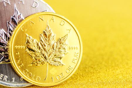 Nahaufnahme von silbernen und goldenen kanadischen Ahornblatt eine Unze-Münzen auf goldenem Hintergrund auf der linken Seite platziert