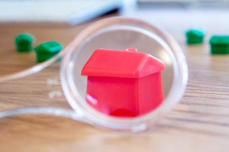 close-up van een klein huis met een vergrootglas, loep als een nieuw dromerig perfect huis voor mij kopen