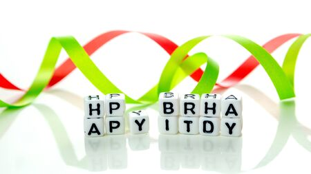 happy birthday special unconventional card made of white cubes with black letters and green birthday decorations on white background