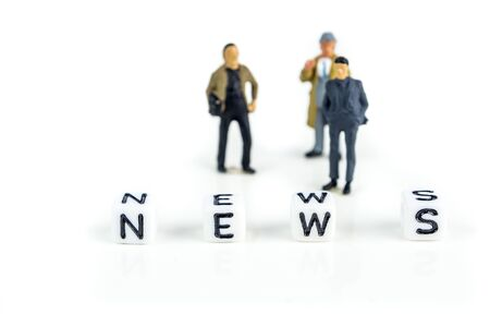 little white cubes with black letters of word news on white background with miniature figurines of businessmen defocused