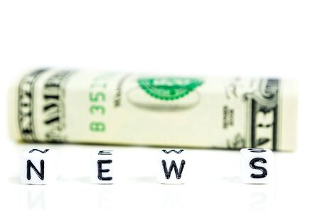 little white cubes with black letters of word news on white background with american dollars in the back defocused