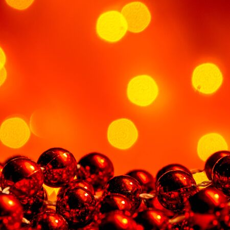 Christmas decoration with snow falling on red background with plenty copy space and orange defocused lights creating cozy atmosphere