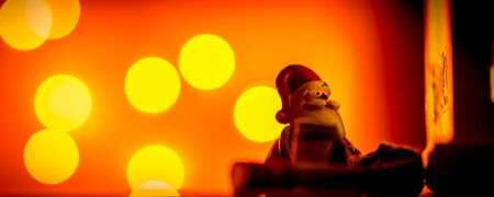 Christmas decoration - Santa Claus with snow falling on red background with plenty copy space and orange defocused lights creating cozy atmosphere