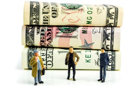 miniature figurines of businessmen standing in front of american dollar banknotes and making economic decisions on white background Imagens