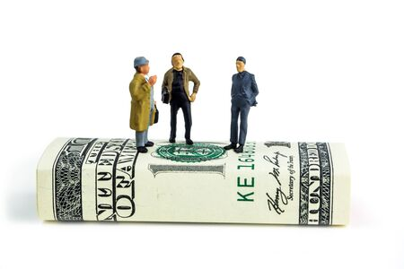 miniature figurines of businessmen standing on one hundred dollar banknote and making economic decisions on white background