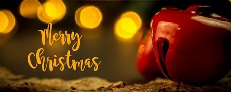 closeup of Christmas decorations, jingle bells with orange colored blurred lights and evening warm atmosphere and dusk background Imagens