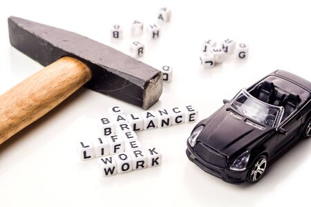 little white dices with black letters forming a crossword with the theme work life balance as equilibrium of professional and personal family life with tools on white background Imagens
