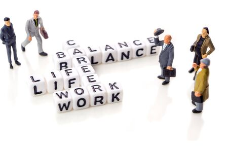 little white dices with black letters forming a crossword with the theme work life balance as equilibrium of professional and personal family life with miniature figurines on white background