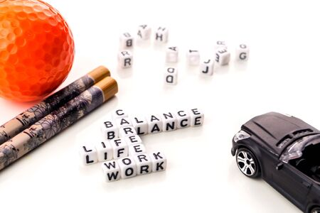 little white dices with black letters forming a crossword with the theme work life balance as equilibrium of professional and personal family life with tools on white background Reklamní fotografie