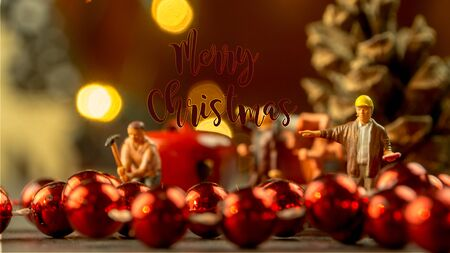 closeup of Christmas decorations, jingle bells and little miniature figurines with orange colored blurred lights and evening warm atmosphere and dusk background
