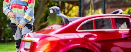 little boy is driving his electro toy car on the backyard of his parents house, action that makes every little boy really happy