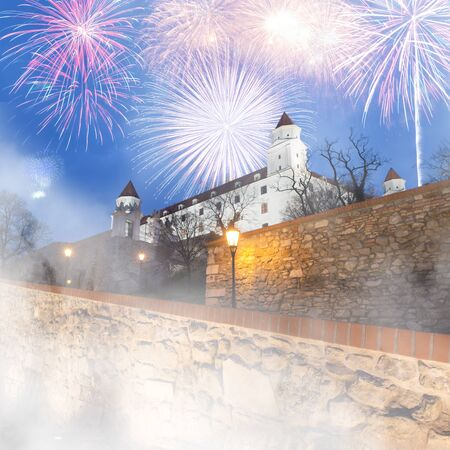 twilight view of lit Bratislava castle  with dramatic sunset cloudy skyline and firework parade during new years fogy night