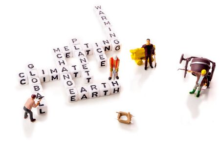 global climate change with planet warming and ice melting words in shape of white cubes with miniature workers figurines with black letters on white background