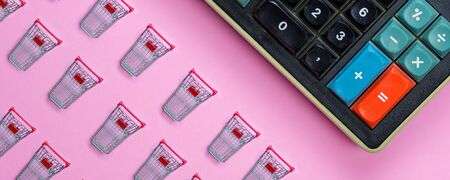 closeup of small miniature shopping carts taken from above with one big old calculator on pink background