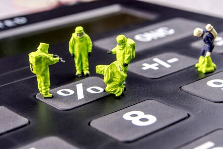 closeup of miniature figurines dressed like members of firemen special team interfering during gas and other chemical accidents with the action monitoring interest rate at historic lows