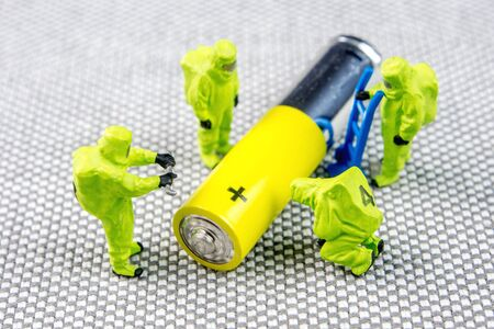 closeup of miniature figurines dressed like members of firemen special team interfering during gas and other chemical accidents, diagnosting little recharchable alkaline recharchable AA battery Stock Photo