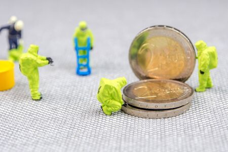 closeup of miniature figurines dressed like members of firemen special team interfering during gas and other chemical accidents with the action protecting/saving euro coins, the debt is growing dangerously