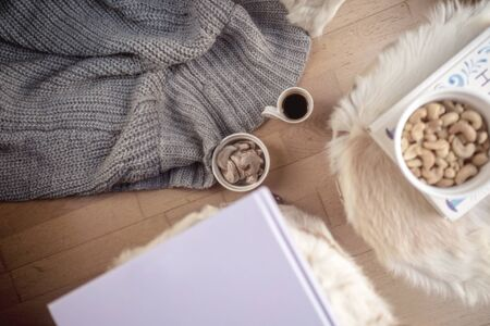 cozy home concept, danish hygge style and their art of happy life, mood of coziness with feelings of wellness and contentment, warm blanket, sweat food, coffee, book and very intime home corner with special lifestyle of well-being and joy