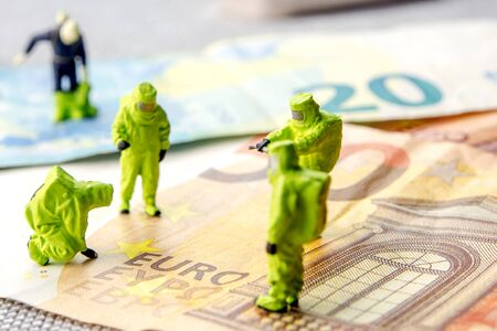 Closeup of miniature figurines with the action protecting euro currency