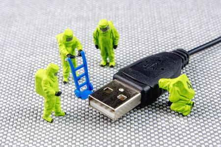 Closeup of miniature figurines diagnosing and solving a IT external computer hardware trouble Stock Photo