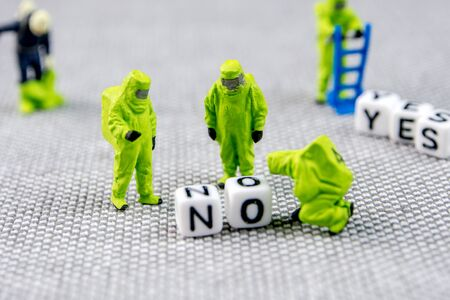 closeup of miniature figurines dressed like members of firemen special team interfering during gas and other chemical accidents with the action protecting/monitoring and solving the problem with toxic word no, substituting it with yes life posture