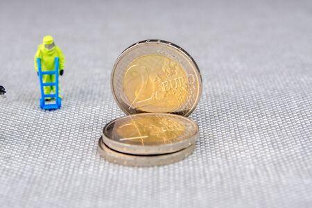 Closeup of miniature figurines with the action protectingsaving euro coins Zdjęcie Seryjne
