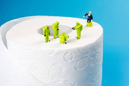 a team of miniature figurines checking a cleanliness of toilet paper, very important to make a desinfection of lavatory and other possibly dirty places in an household