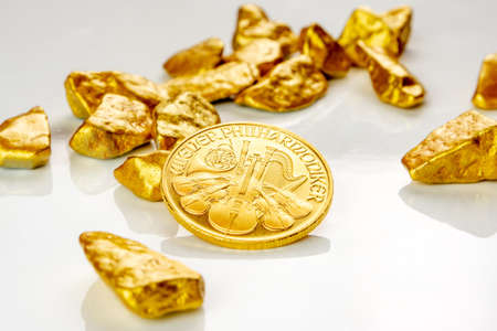 golden austrian philharmoniker one ounce coin laying on a heap of golden nuggets, golden ore on white background isolated with plenty copy space