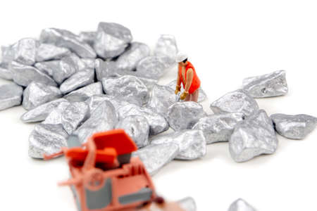 miniature figurines digging silver , platinum ore as team work on white background