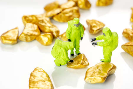 bio hazard special forces miniature figuriens in special green suits making an inspection whether the gold or precious metals is safe and good investment Stock Photo