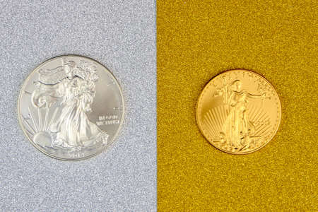 silver eagle and golden american eagle one ounce coins laying on silver and golden background, image split in two halves Stock Photo - 155220819