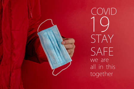 man in red jacket is using a protective mask against corona virus on red background, red color symbol of high alert and stop sign against the disease, COVID-19 SARS, SARS-CoV Stock Photo