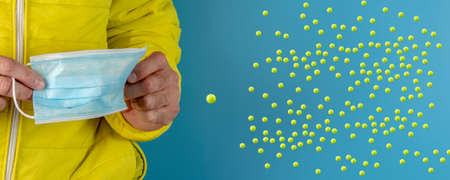 man in yellow jacket is using a protective mask against corona virus on blue background, high alert and the battle against the disease, COVID-19 SARS, SARS-CoV, virus 2020