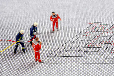team of firefighters and doctors solving a difficult maze problem, finding best possible solution, five miniature figurines standing on complicated maze and thinking about the exit strategy