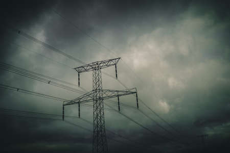 silhouette of transmission towers, power tower, electricity pylon, steel lattice tower at twilight in Europe with moody dusk heavy atmosphere, high voltage pillar, overhead power line, industrial background