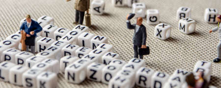 set of popular crypto coins words forming thematical crossword made of white cubes with black capital letters and miniature businessmen figurines having a team meeting, bitcoin, altcoins, ethereum, ripple, lumen, eos, litecoin, omisego, monero
