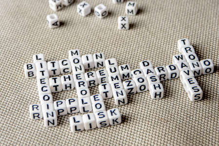 set of popular crypto coins words forming thematical crossword made of white cubes with black capital letters, bitcoin, altcoins, ethereum, ripple, lumen, eos, litecoin, omisego, monero