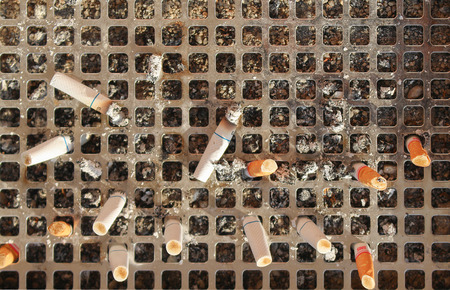discarded metal: Discarded cigarette butts in a metal public ashtray  Stock Photo