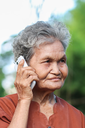 Asian old woman talking on mobile phone  photo