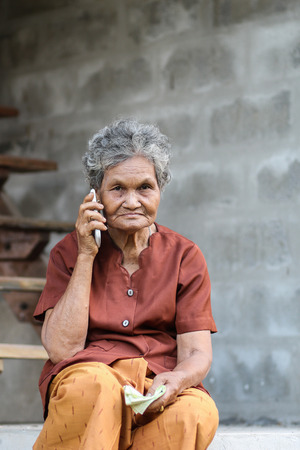 Asian old woman talking on mobile phone JPG photo