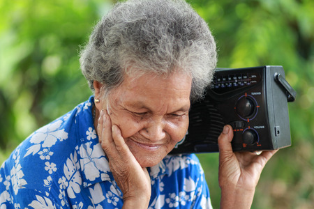 Old Woman Listening To Music With A Vintage Radio, outdoor