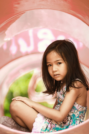 dreary: Asian girl Sitting at the playground And joyless
