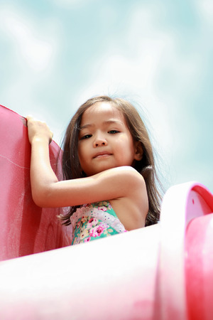 attractive little girl on outdoor playground equipment Stock Photo